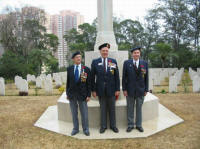 L to R: Aubrey Flegg(WG), Larry Stebbe(WG) and John Lowe(RRC) standing in front of the Stone of Remembrance at Sai Wan Cemetery